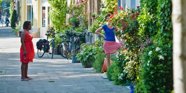 2 bewoners slaan praatje met elkaar in straat met veel groen en geveltuintjes