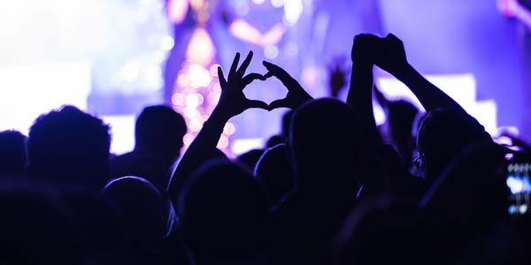 Concertgangers vormen hartje met hun handen