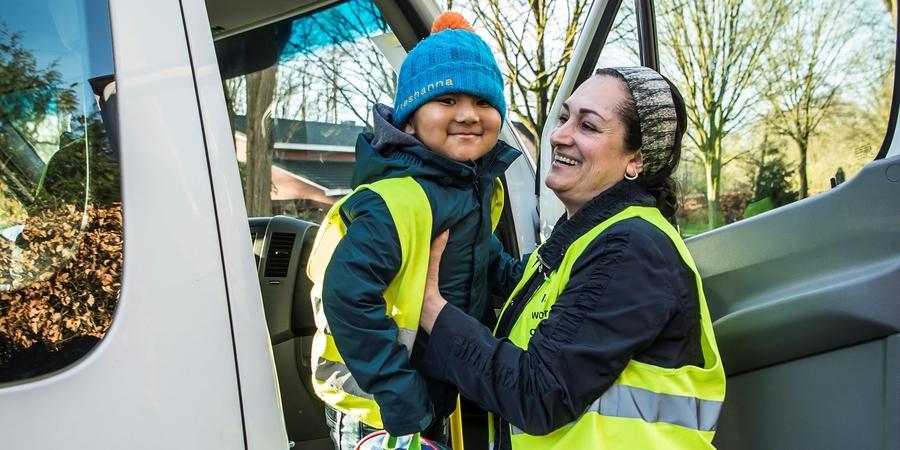 busbegeleider helpt kind uit schoolbus