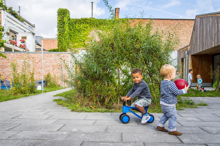Een wilgenhut met op de voorgrond twee kinderen: eentje speelt met een bal, eentje zit op een fiets