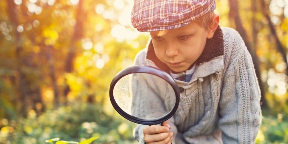 Jongetje dat op onderzoek gaat met een vergrootglas in de hand in een park