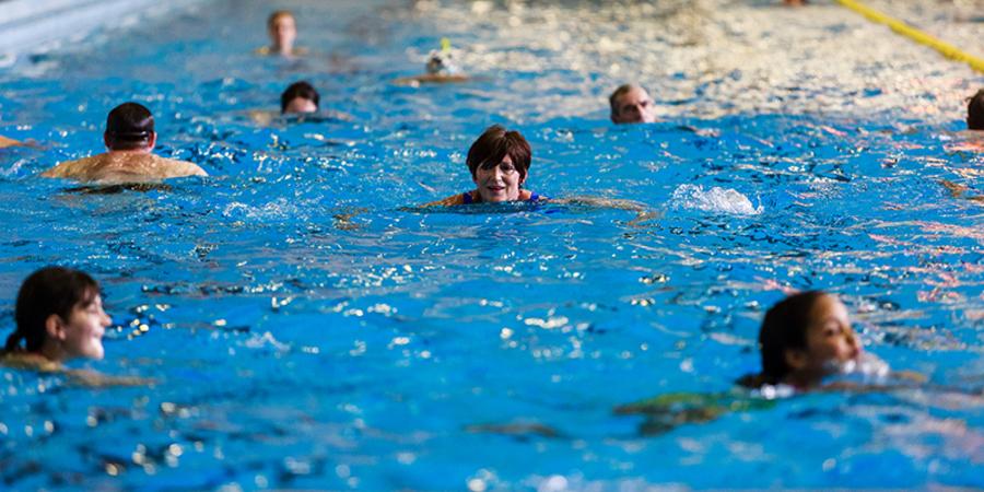 Verschillende zwemmers in een zwembad