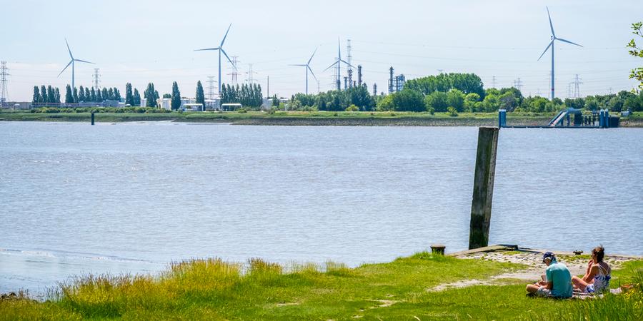 Een man en een vrouw zitten op een stukje groen langs de Schelde. Aan de overkant staan enkele windmolens.