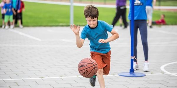 Een jongen speelt basket op de speelplaats