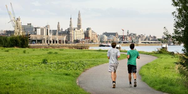Twee joggers lopen langs de Scheldekaaien op Linkeroever met zicht op de Antwerpse skyline en kathedraal