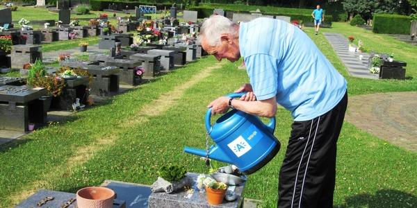 Een man begiet de bloemstukken met een Wilrijkse gieter