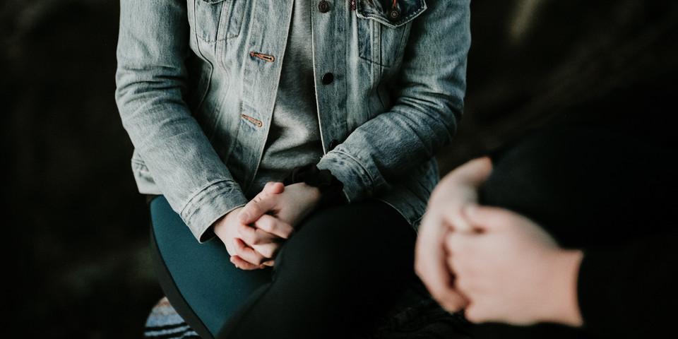 Een vrouw zit met gekruiste benen tegenover een andere persoon.
