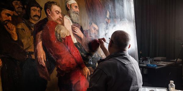 restaurator Marc Leenaerts restaureert het schilderij van Emile Godding.