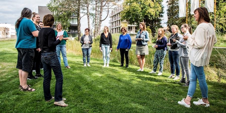 Een groep kinderbegeleiders volgen een workshop rond buitenactiviteiten