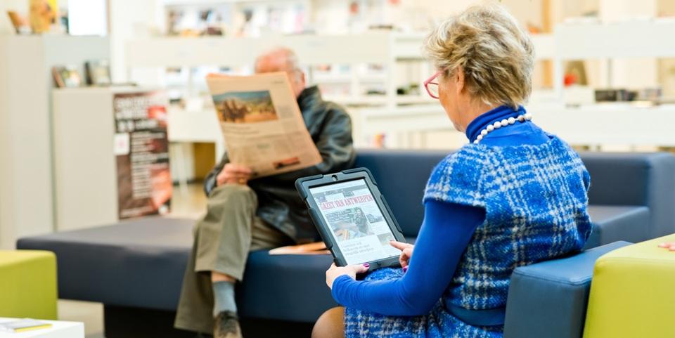 Vrouw leest de krant op tablet in de bibliotheek