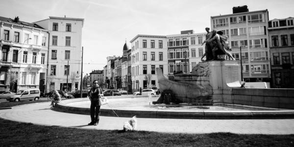 De Lambermontplaats met standbeeld, waterpartij en wandelaar met kleine hond.