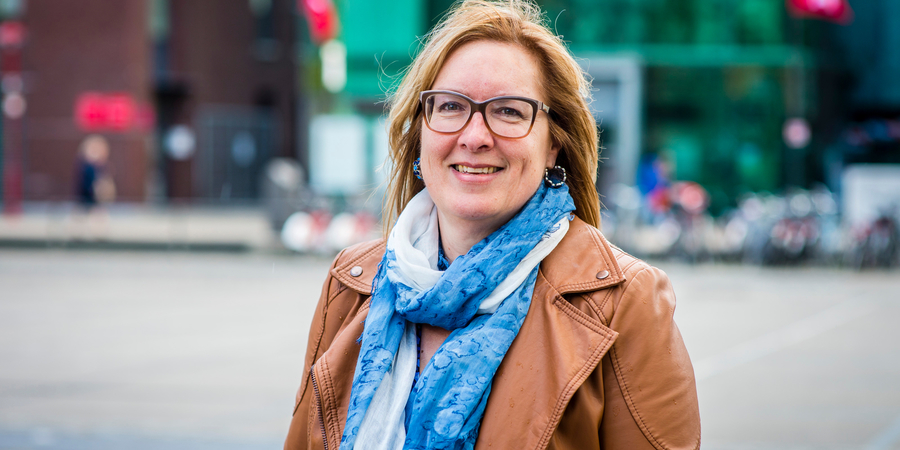 Ombudsvrouw Karla Blomme staat op het De Coninckplein en kijkt in de camera.