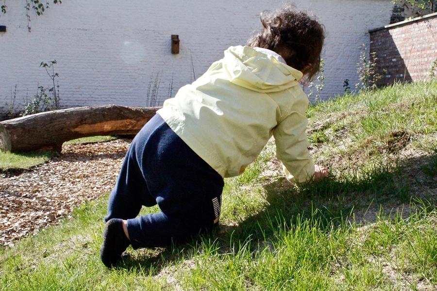 Kind klimt over groene heuvel