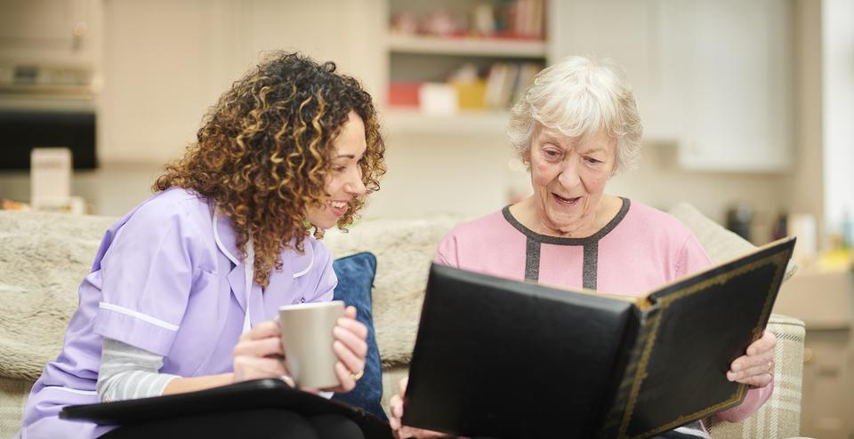 Oudere dame die een fotoboek bekijkt. Daarnaast zit een verpleegster