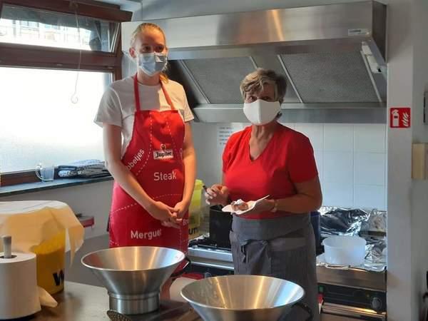 twee mensen met mondmasker in een smoutebollenkraam