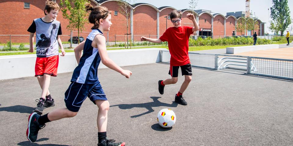 Drie kinderen voetballen op een pannavoetbalveldje in het Regatta Urban Sports Park in Antwerpen-Linkeroever.