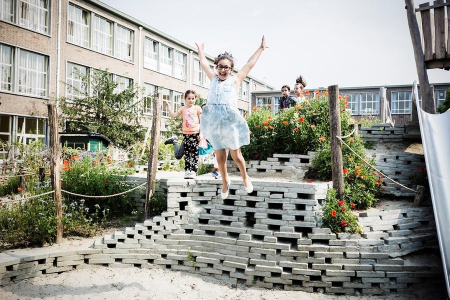 Een meisje springt van een stenen heuvel