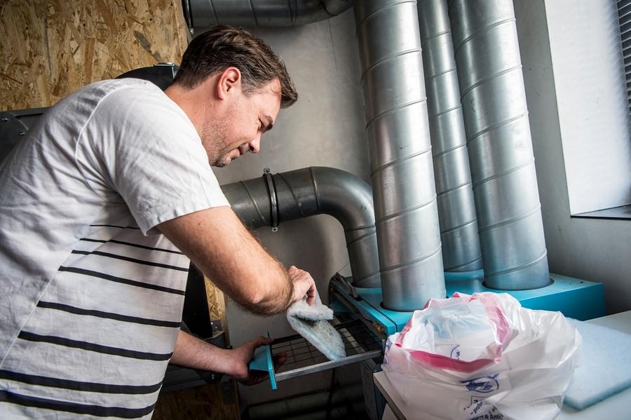Een man steekt het filterdoek in een vuilzak.