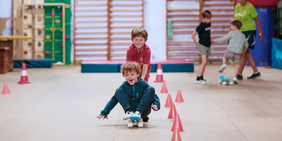 Lachende jongen die zit op een skateboard terwijl een andere jongen hem voortduwt