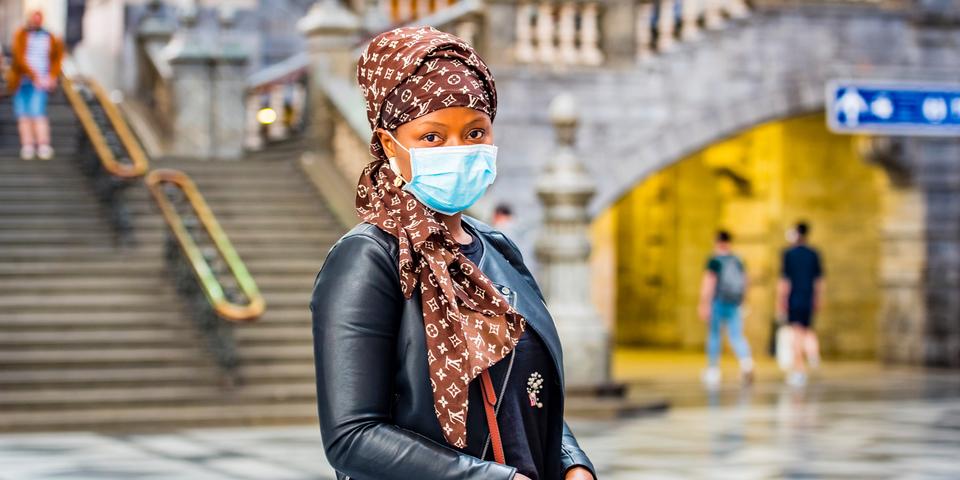 Een Afrikaanse vrouw met leren jas en mondmasker staat in de inkomhal van het Centraal Station.
