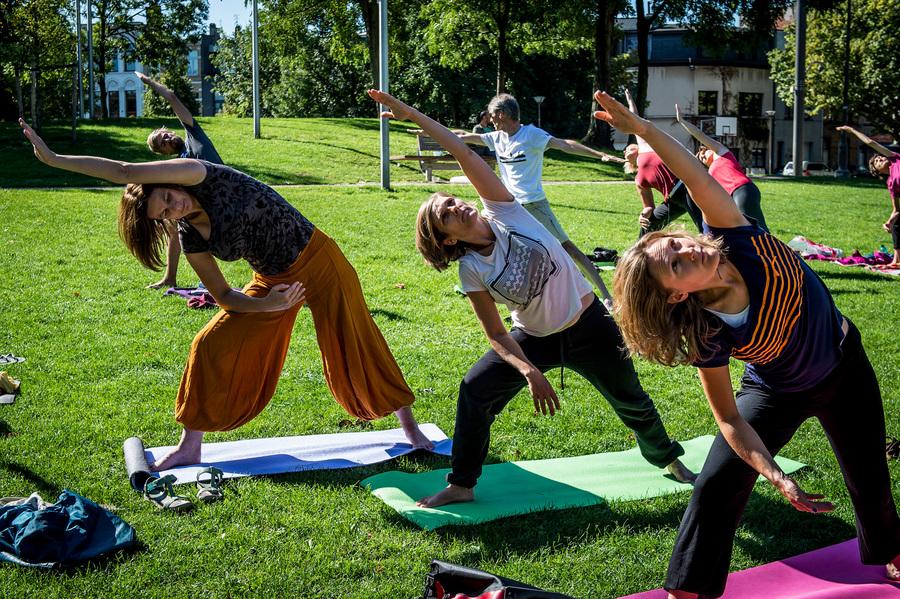 Drie vrouwen doen een yoga-oefening in een park
