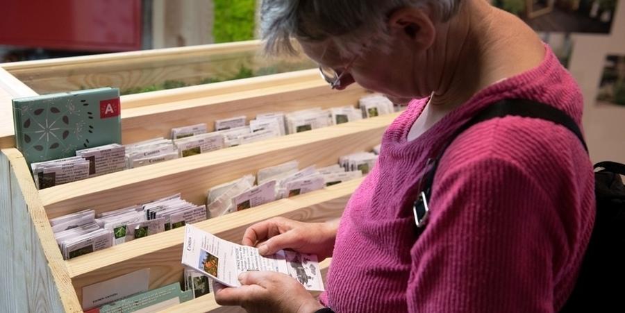 Een vrouw bekijkt een pakje zaadjes in de zadenbib en leest de bijbehorende uitleg.