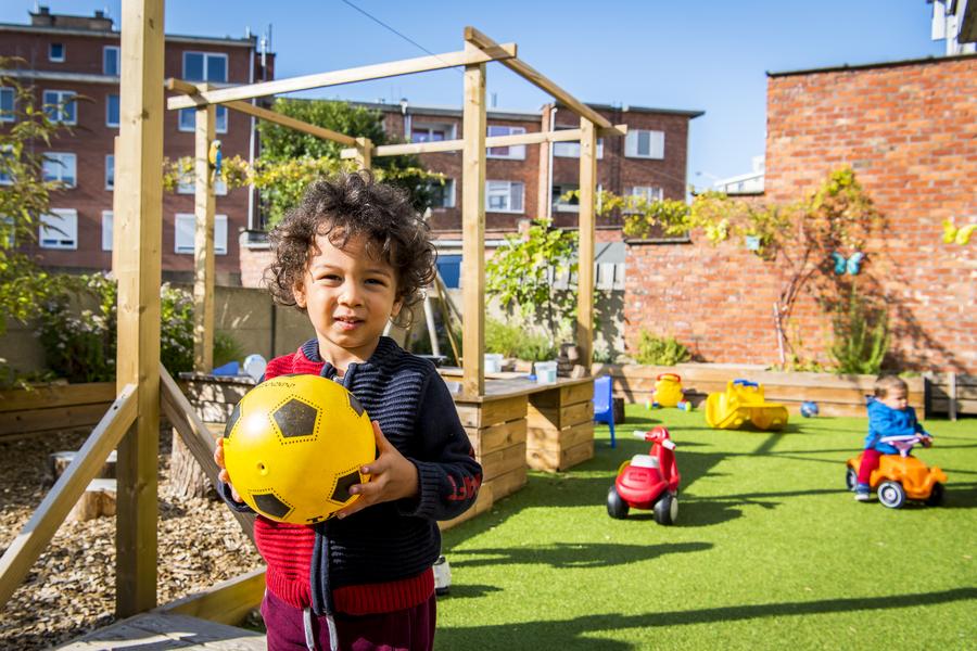 Jongen met bal staat in de nieuwe buitenruimte