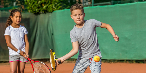 kinderen spelen tennis op een tennisveld