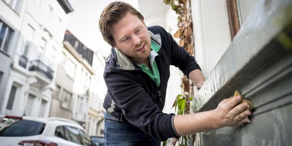 Man poetst vensterbank