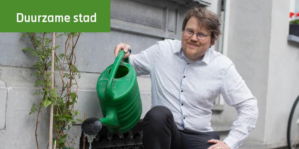 Jo, communicatiemedewerker EcoHuis, geeft water aan een gevelplant