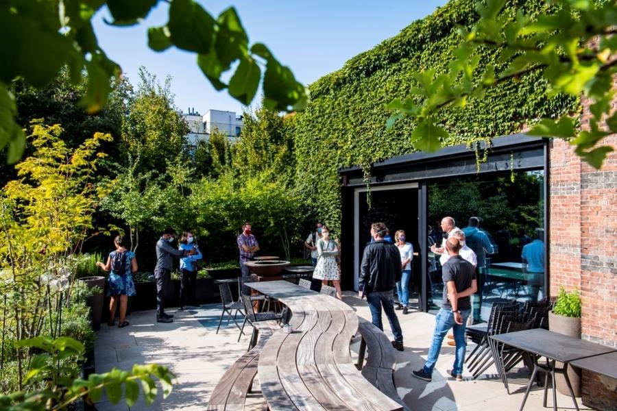 Mensen bekijken een ingesloten, groen en zonnig terras