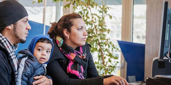 Man en vrouw met kindje gebruiken een pc in de bib