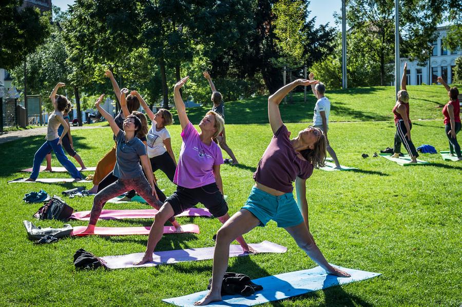 Groep vrouwen doen een yoga-oefening in een park