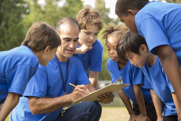 Trainer knielt en geeft instructies via trainersbord aan groepje van vijf kinderen
