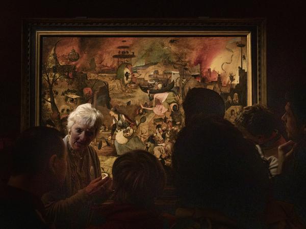 Verschillende mensen staan voor het schilderij 'Dulle Griet' van Pieter Bruegel de Oude.