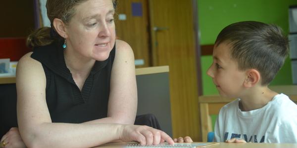 Vrijwilliger Sandra Peeters helpt Elvidin met lezen