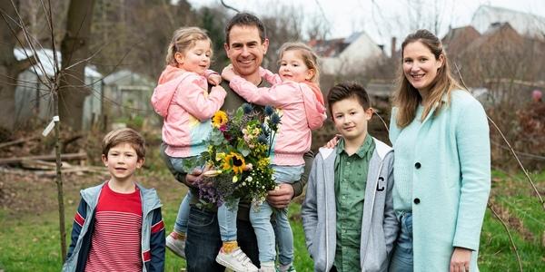 Een gezin poseert met een boeket bloemen op de plukweide van Buitengewoon Grondig