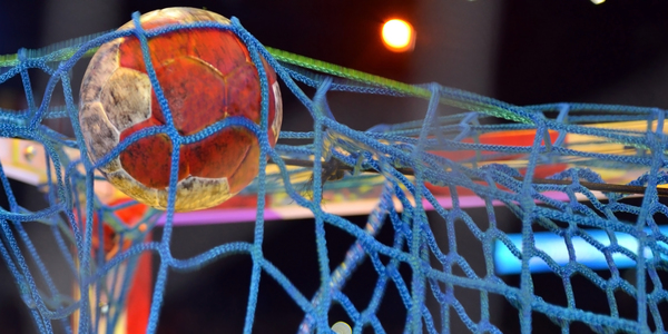 Een handbal vliegt tegen het net.