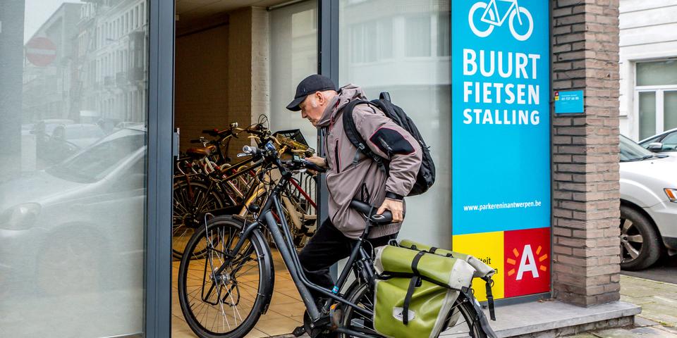 Man zet zijn fiets in een buurtfietsenstalling