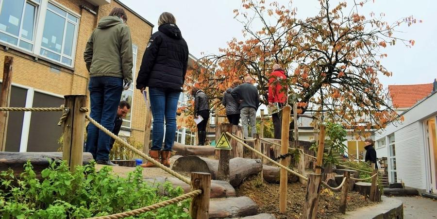 Groene speelplaats met waarschuwingsbordje voor uitglijdingsgevaar bj de boomstammen