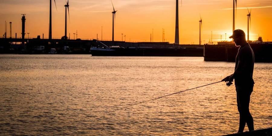 Een man is bij zonsondergang aan het vissen in de Schelde.