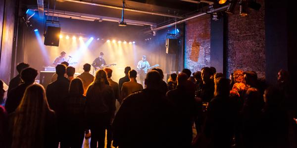 Jonge band treedt op in jeugdhuis met veel publiek vlak voor het podium