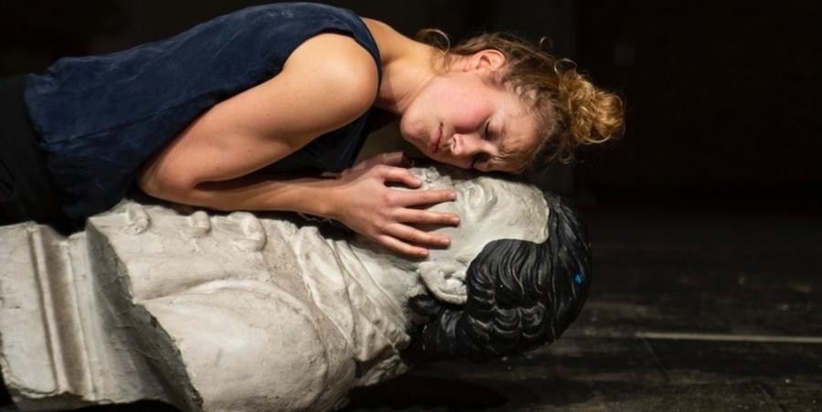 Een vrouw omhelst een borstbeeld terwijl ze op de grond ligt.