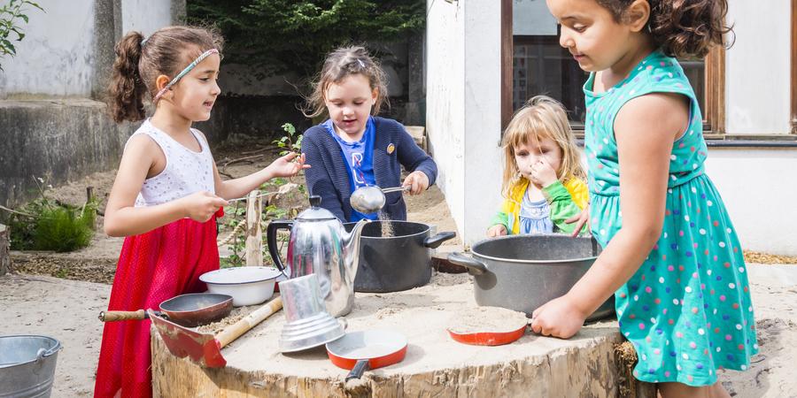 Meisjes spelen met potten en pannen in een zandbak met boomstamtafels