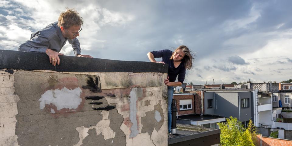 Een technisch adviseur geeft advies over dakbekleding op een dak.