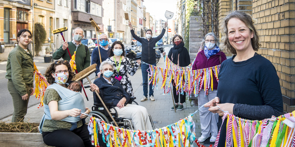 Vrijwilligers van Posthof poseren met vlaggenwimpels