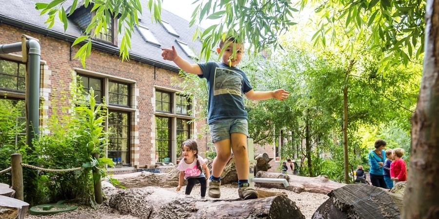 Een jongen balanceert over een liggende boomstam
