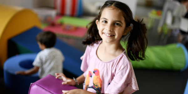 Een meisje houdt een speelmatje vast en kijkt al lachend in de lens.