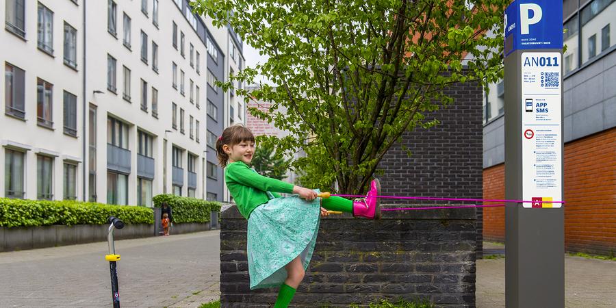 Meisje speelt met springtouw aan parkeerautomaat