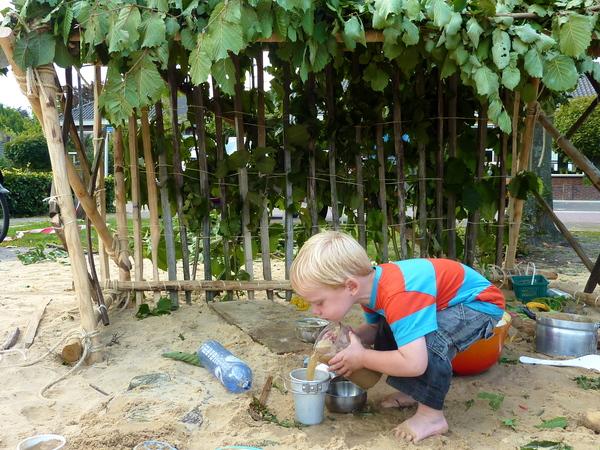 Jongen experimenteert met water, zand en andere natuurlijke materialen